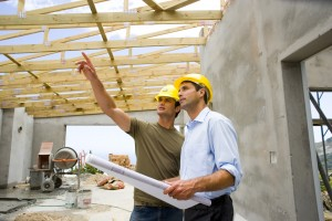 Two men holding blueprints standing in a building structure