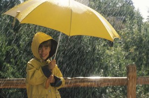 Child in a raincoat and umbrella standing in the rain