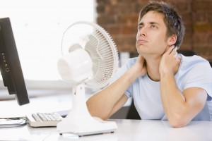 Man sitting in front of a fan trying to cool off